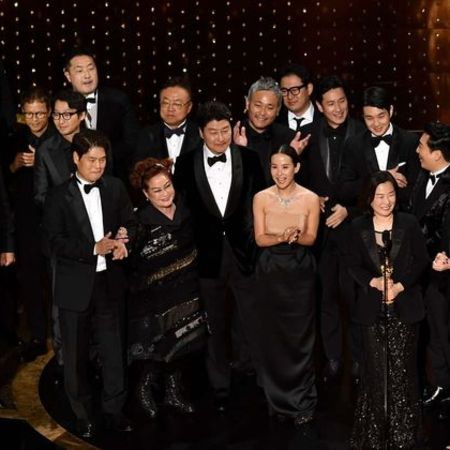 The cast and crew of Parasite giving an acceptance speech